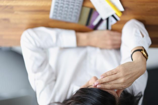 Mulher deprimida e cansada sentada sobre cartões bancários de plástico e calculadora, vista de cima, conceito de dívida bancária