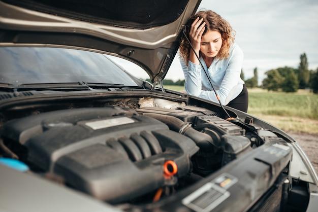 Mulher deprimida olhando para o motor, carro quebrado com capô aberto. problemas com o veículo