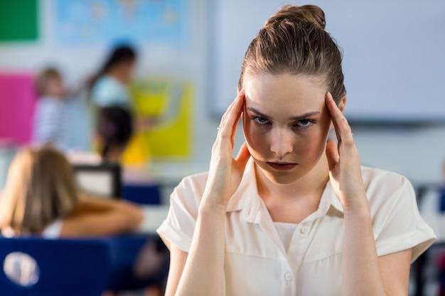 Mulher deprimida professora tocando sua cabeça na turma escolar