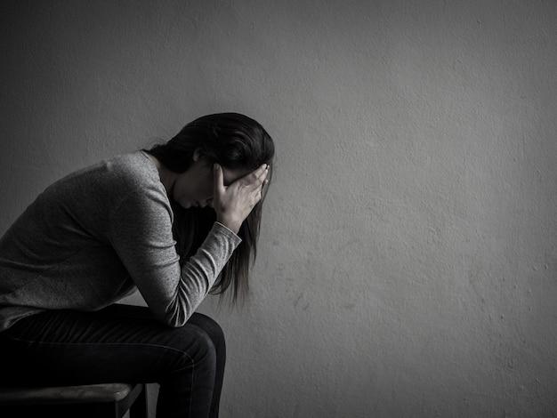 Mulher deprimida que senta-se em uma cadeira na sala escura em casa.