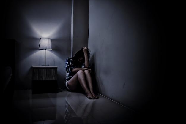 Mulher deprimida sozinha no quarto escuro. problema de saúde mental, ptsd é transtorno de estresse pós-traumático.