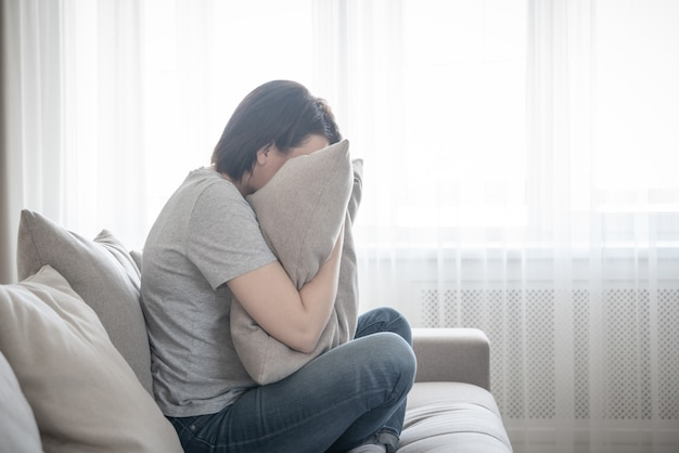 Mulher deprimida triste chorando no conceito de travesseiro, solidão e tristeza