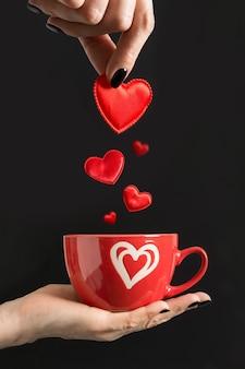 Mulher derrama corações vermelhos na xícara de café. isolado em preto. conceito de amor. vertical. cartão de dia dos namorados. fechar-se.