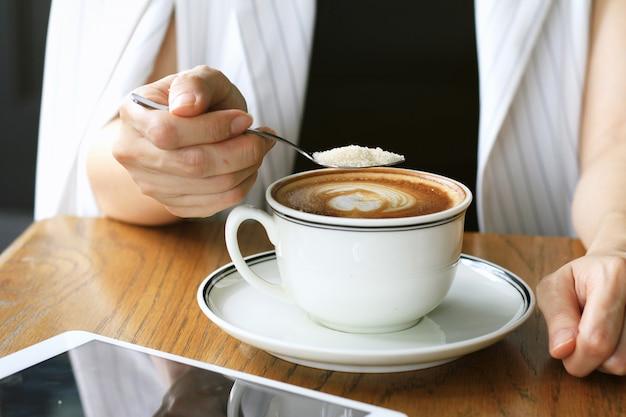 Mulher derramando açúcar na xícara de café. conceito viciado em açúcar.