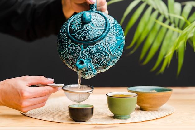 Mulher derramando chá em copo através de peneira