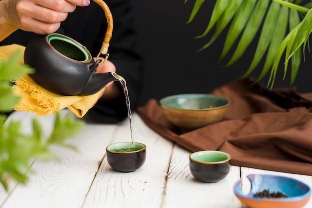 Mulher derramando chá em copo pequeno