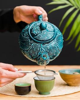 Mulher derramando chá em copo usando peneira