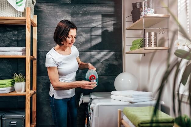 Mulher derramando detergente líquido na tampa da garrafa