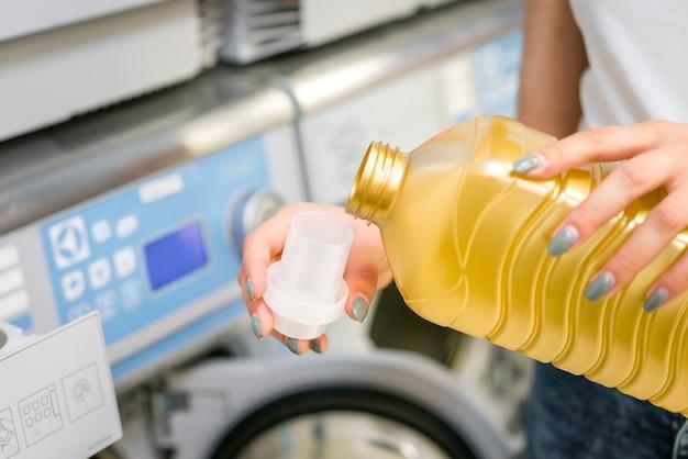 Mulher derramando detergente na tampa