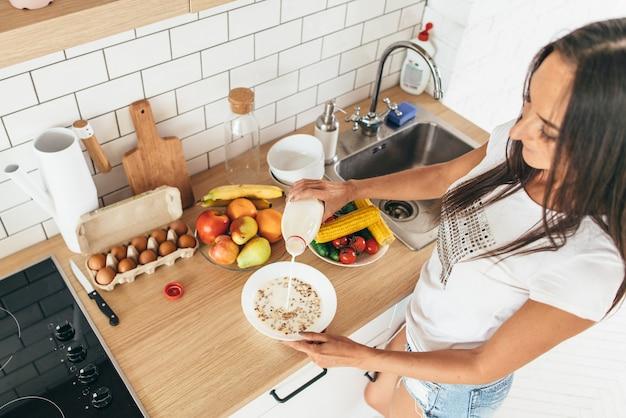 Mulher derramando leite no prato com flocos de carvalho.