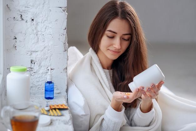 Mulher derramando medicação, comprimidos e cápsulas na mão