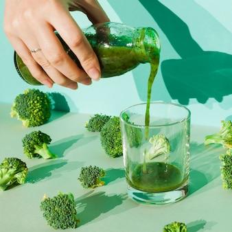 Mulher derramando smoothie de brócolis em vidro