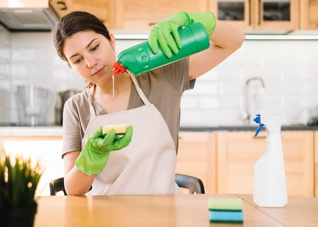 Mulher derramando solução de limpeza