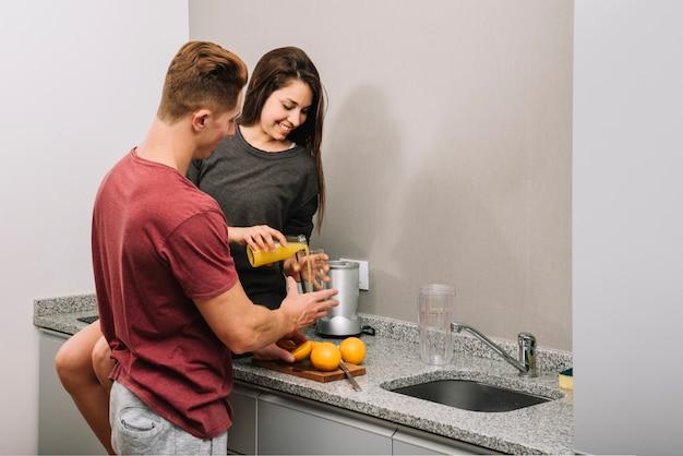 Mulher derramando suco de laranja no copo de homem