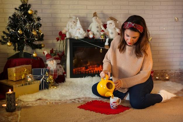 Mulher derramando um café quente ao lado da lareira com atmosfera de natal.