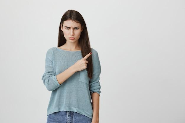 Mulher desapontada irritada, franzindo a testa, apontando o canto superior direito do dedo