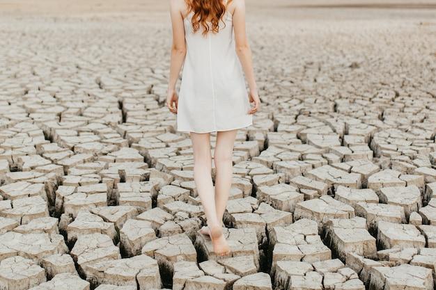 Mulher descalça andando no chão do lago seco.