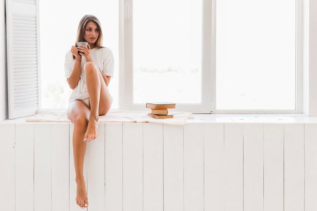 Mulher descalça com copo perto da janela
