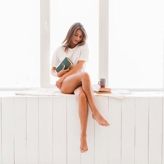 Mulher descalça com livro sentado no peitoril da janela