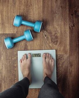 Mulher descalça é pesada na balança no chão com halteres. conceito de fitness