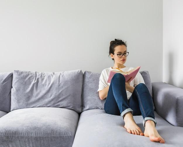 Mulher descalça escrevendo no livro