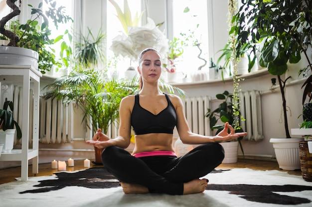 Mulher descalça meditando em casa