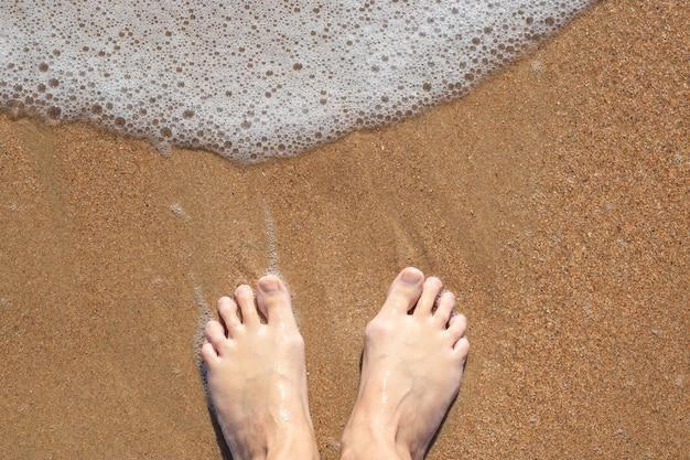 Mulher descalça na areia com espuma do mar