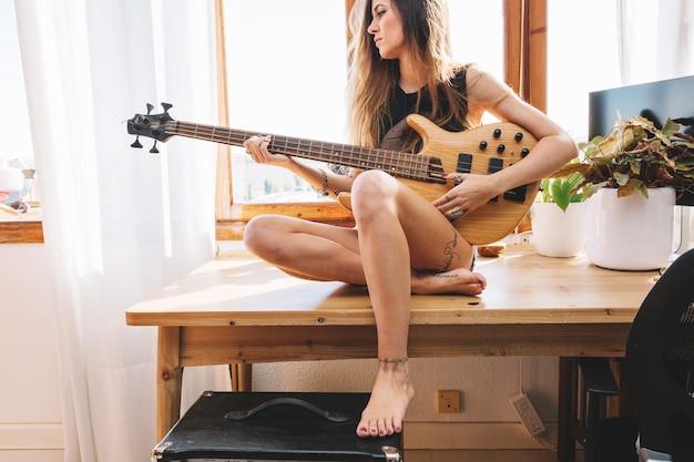 Mulher descalça tocando violão na mesa