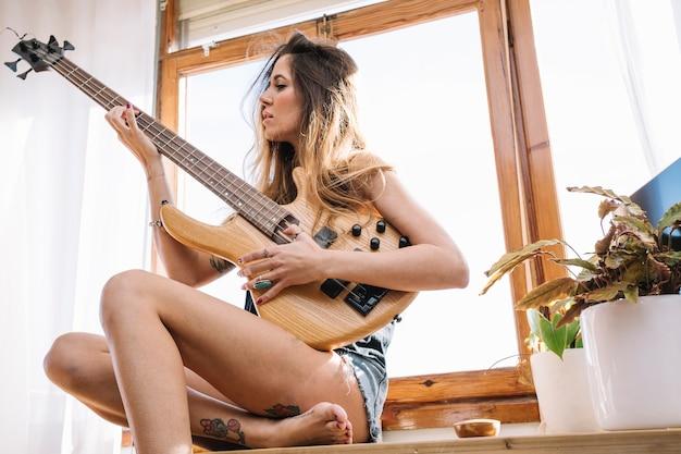 Mulher descalça tocando violão perto da janela
