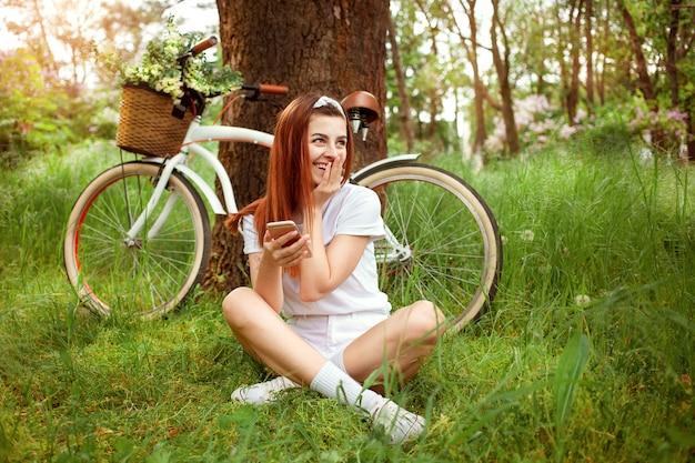Mulher descansa na natureza. uma garota se senta na grama com seu telefone. bicicleta para alugar e alugar por dia. verão primavera. tecnologia, internet para se comunicar com amigos nas férias, redes sociais. sorridente