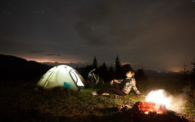 Mulher descansando à noite, acampar perto da fogueira, barraca do turista, bicicleta sob o céu cheio de estrelas