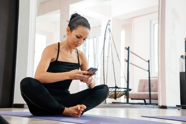 Mulher descansando após o treino em casa com o telefone. jovem desportiva depois de praticar ioga, pausa
