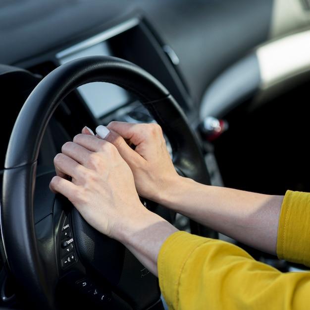 Mulher descansando as mãos no volante