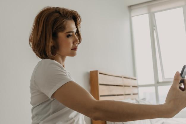 Mulher descansando e relaxando no quarto com seu smartphone na mão