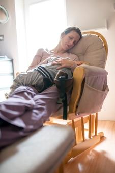 Mulher descansando em uma cadeira com seu filho