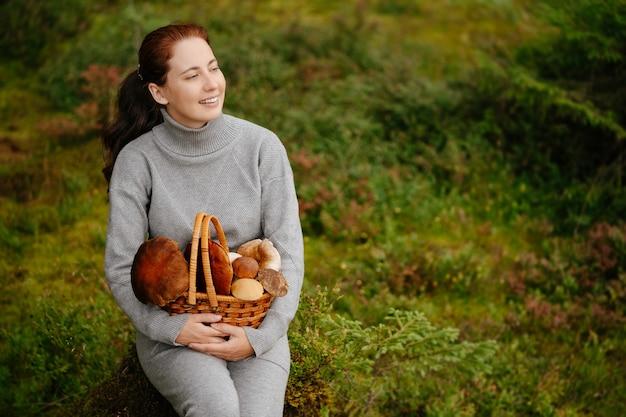 Mulher descansando em uma floresta verde com cesta de cogumelos conceito de ecoturismo