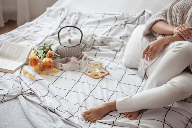 Mulher descansando na cama com chá, um livro e um buquê de tulipas