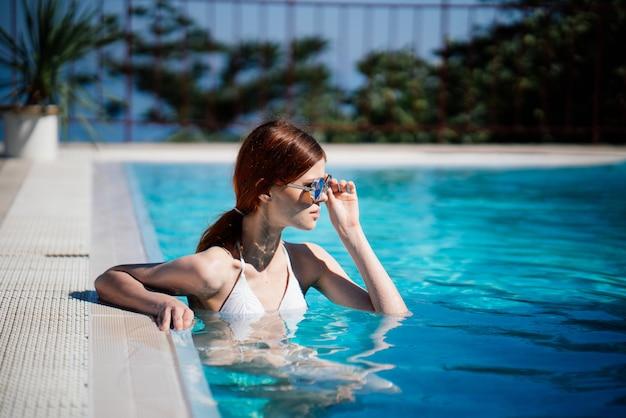 Mulher descansando na piscina azul