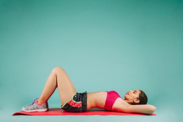 Mulher descansando no chão após o treinamento