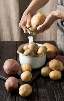 Mulher descascando algumas batatas cruas