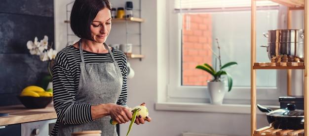 Mulher descascando maçãs na cozinha