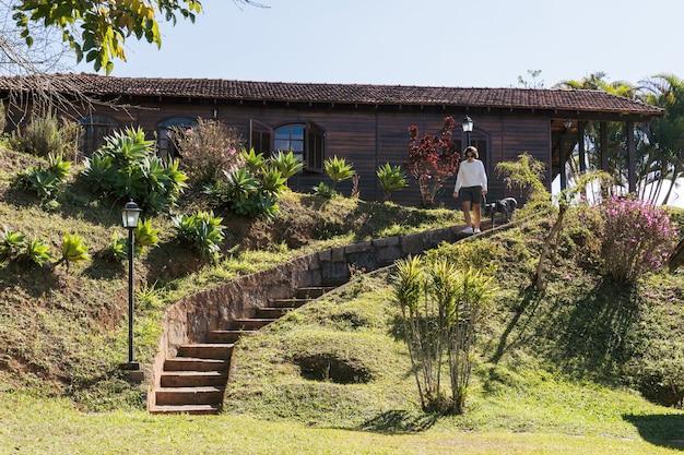 Mulher descendo as escadas do quintal com uma casa de cachorro pit bull no meio da natureza