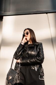 Mulher descolada e elegante e bonita hippie em roupas de rock preto da moda com jaqueta de couro e óculos de sol redondos vintage perto da parede na cidade