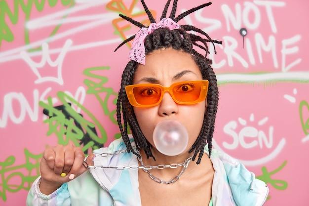 Mulher descolada e moderna com tranças de cabelo, sopra chiclete segura uma corrente de metal pendurada no pescoço vestida com roupas da moda posa contra uma parede de grafite colorido