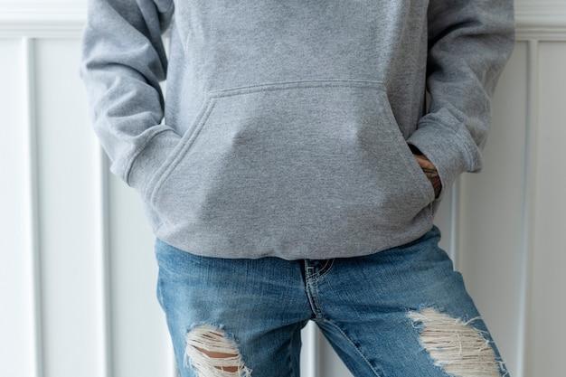 Mulher descolada em um moletom cinza com jeans rasgado