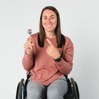 Mulher descolada em uma cadeira de rodas com um adesivo de voto no dedo indicador