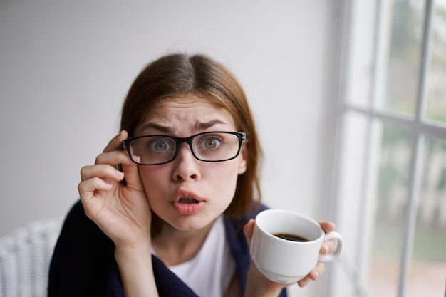 Mulher desconcertada em copos tem uma xícara de café nas mãos