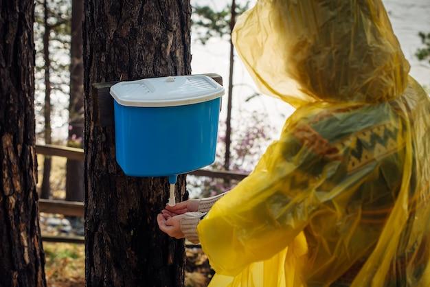 Mulher desconhecida com capa de chuva amarela lava as mãos na bacia pendurada na árvore. manhã chuvosa no acampamento turístico na floresta perto do rio.