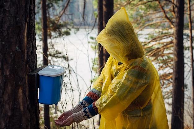 Mulher desconhecida com capa de chuva amarela lava as mãos na bacia pendurada na árvore.