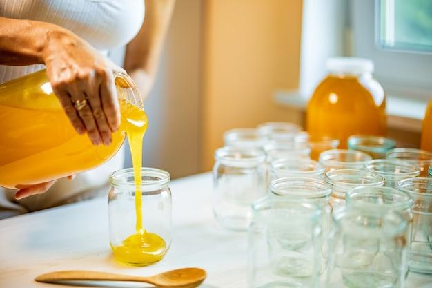 Mulher desconhecida derrama mel dourado em potes transparentes e vazios em cima de uma grande mesa de madeira branca em um dia ensolarado